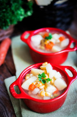 Chicken noodle soup with vegetables in red bowl on rustic table