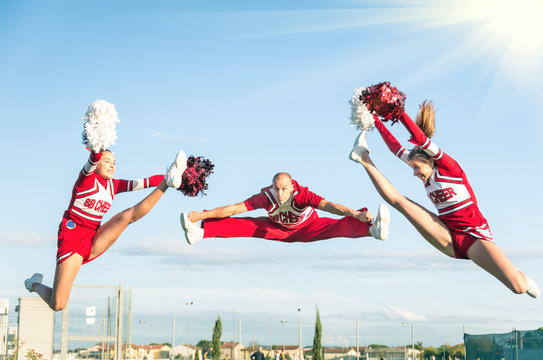Cheerleaders team performing a Jump with male Coach
