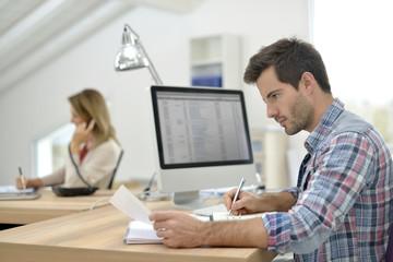 Man working in office in front of desktop