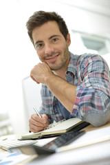 Smiling office worker sitting at desk