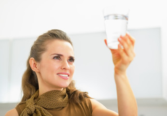 Young housewife looking on glass of water