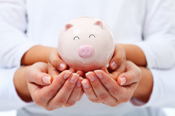 Financial education concept - adult and child hands holding pigg