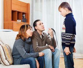Mother and  father with belt scolding  son