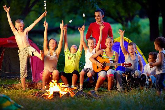 laughing kids friends having fun around campfire