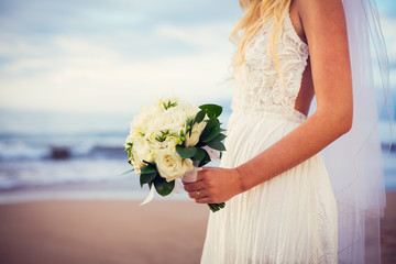 beautiful bride standing by the beach at sunset