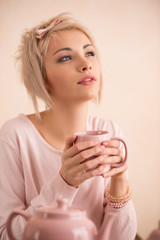 Young beautiful blond woman having tea-party.