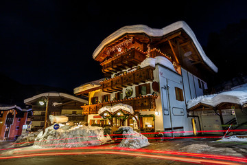 Fototapete - Traffic Trails on Illuminated Street of Madonna di Campiglio at