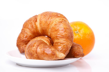 Two croissants on a plate and an orange