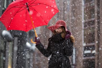 Woman with umbrella on snowy street