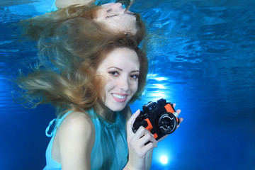 Woman underwater with photo camera