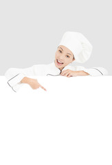 Fototapeta smiling  young woman chef pointing  with blank board