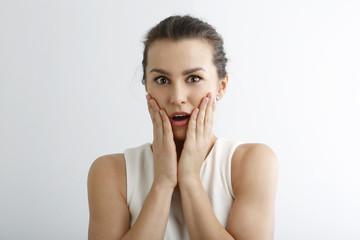 Young woman looking surprise against white background