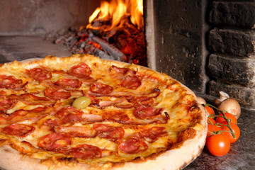 Baked tasty pizza with salami and bacon near oven