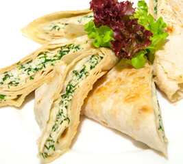 Grilled pita bread with feta cheese and herbs on plate,