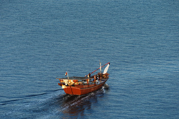 Dubai, UAE: A wooden Dhow Sails into the Creek at Dawn