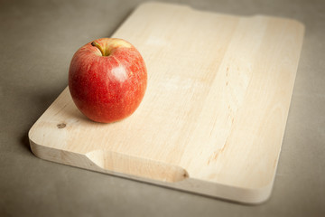 apple on wooden cutting board