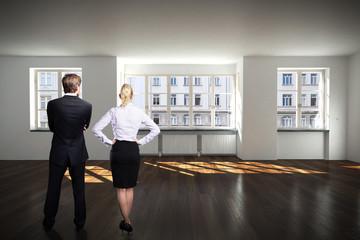 Geschäftsleute stehen in leerem Büroraum