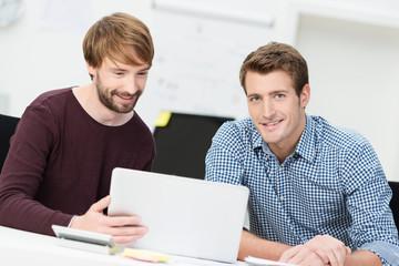 zwei kollegen am arbeitsplatz schauen auf laptop