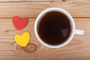 Cup of coffee and two hearts on a wooden background.