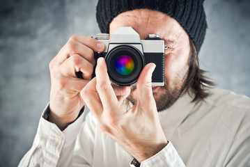 Businessman taking photo with vintage film camera