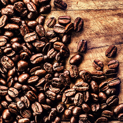 Coffee on grunge wooden background closeup. Roasted  coffee bean