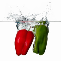 Fresh Red and Green Peppers Splash in Water Isolated on White Ba