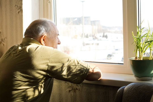 Lonely old man staring out of a window