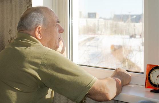 Senior man standing reminiscing at a window