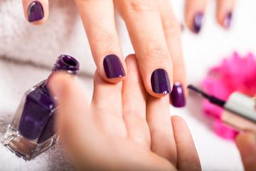frau bekommt ihre nägel in lila lackiert nagelstudio maniküre