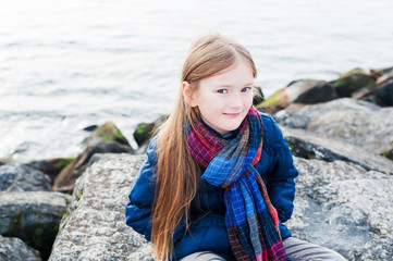 Outdoor portrait of a cute little girl next to lake