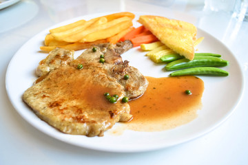 pork chop steak and gravy on white dish