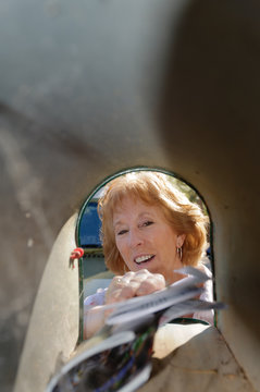 older woman taking mail out of mailbox