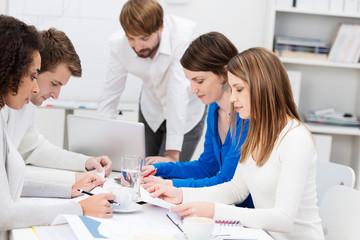 arbeitsgruppe liest konzentriert in den unterlagen