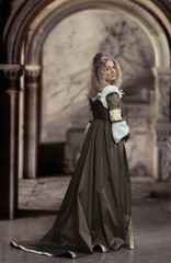 Woman in medieval dress looking back, antique interior