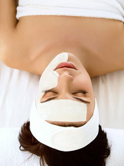 Beautiful Woman With Cosmetic Mask on Face. Girl Gets Treatment