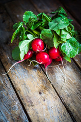 Radishes on rustic wooden background