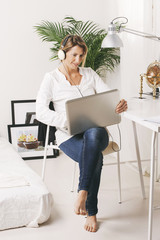 Beautiful mature business woman working with laptop in home.