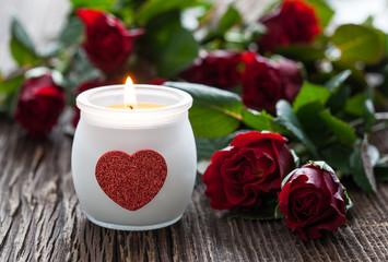 Rosen mit Kerze auf Holz