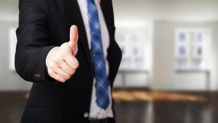 Geschäftsmann vor leerem Büro mit Daumen-Hoch-Geste