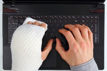Arbeit am Notebook mit Handverletzung
