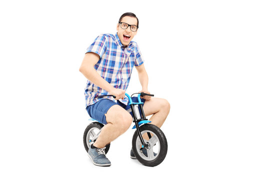 Funny young man riding a small bike
