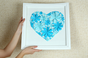 Woman hanging up picture with heart from paper flowers