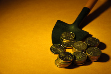Coins with shovel on brown background