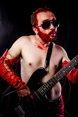 Fun, guitarist with electric guitar black, wearing face paint an