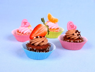 Appetizing cupcakes with angel, heart, tangerine, strawberry