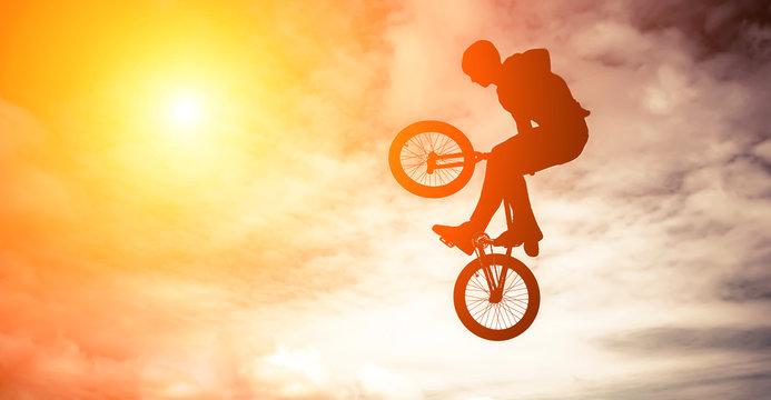 Man doing an jump with a bmx bike against sunshine sky.