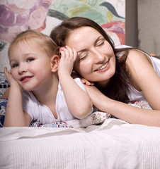 Portrait of happy family, mother and daughter in bed at home