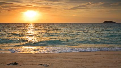 Sea wave hit the sand at sunrise