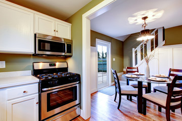 White and olive kitchen and dining room interior