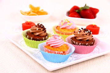 Four appetizing cupcakes on white plate